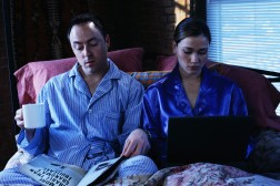 Business Couple Working in Bed