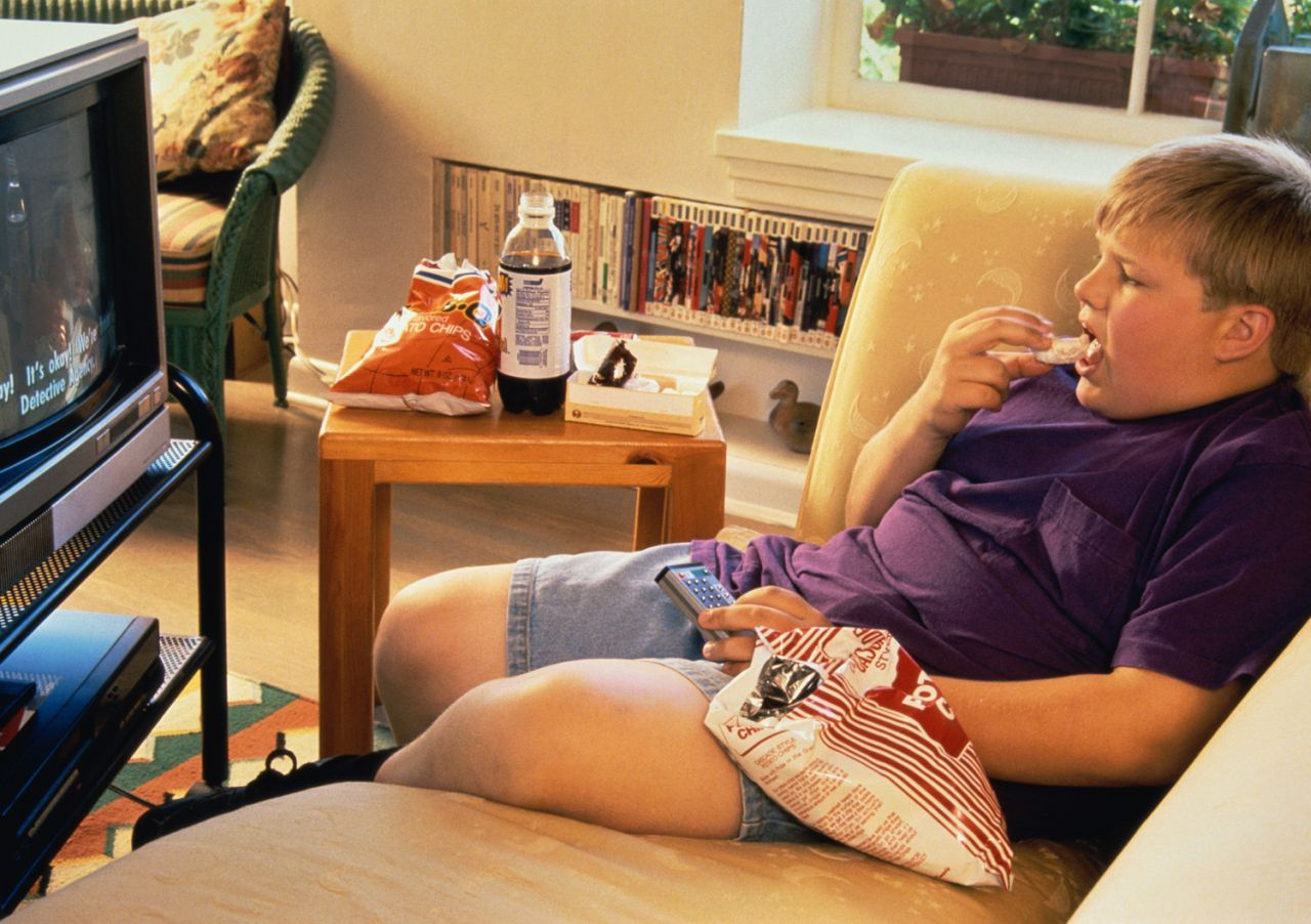 Image: child eating chips, watching television